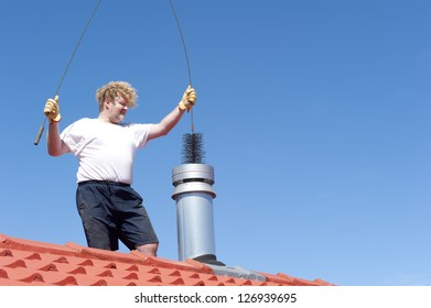 Man standing on rooftop of residential building to clean metal chimney of house with sweeper, with blue sky as background and copy space.