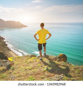 Man standing on sea and mountain landscape. Conceptual and emotional scene.