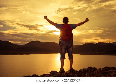 man standing on the shore of a mountain lake and raises his arms to the sky