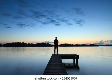 Man standing on a small jetty looking over a Dutch lake during a calm, blue sunset.