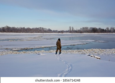 A man standing on the snowy shore of an icy river. A person on a snow shore of a Siberian river. A freezing river.
