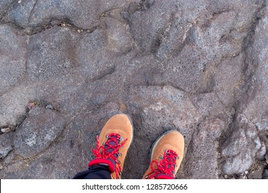 man standing on solidified lava, volcanic base, volcanic rock