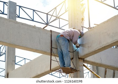 Man standing on steel scaffold and welding structure of factory in construction site, High risk occupation.