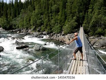 Man standing on a suspension bridge
