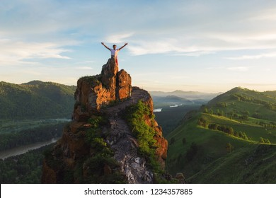 Man standing on top of cliff in summer beauty day in Altai mountains