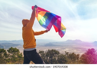 Man standing on top of the hill and holding the LGBT pride flag