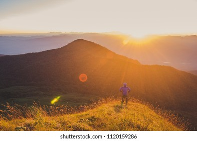 Man Standing on top mountain, Travel Lifestyle success concept adventure active vacations outdoor.