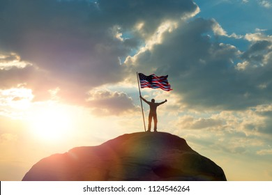 the man is standing on the top of the mountain, holding his hands up with the flag of the US America against the sunset. Business concept idea, success and achievements, career ladder, victory.