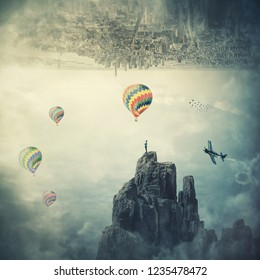 Man standing on the top of a mountain at the border of two parallel worlds a city above sky and hot air balloons flying. Beautiful mystical scene, imaginary world.