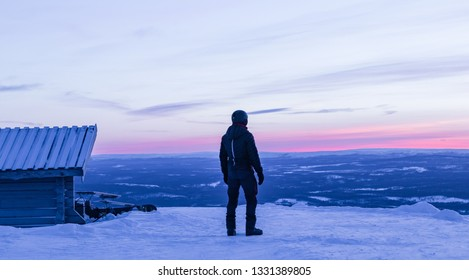 Man standing on top of the mountain at Idre Fjall, Sweden watching a pink sunset on a cold winter evening after a full day of snowboarding. View of the valley below with frozen trees and mountains.