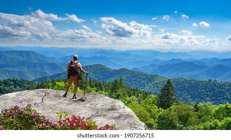 Man standing on top of the mountain relaxing and  enjoying beautiful summer mountain landscape. A panoramic view of the Smoky Mountains from the Blue Ridge Parkway in North Carolina. Near Asheville.