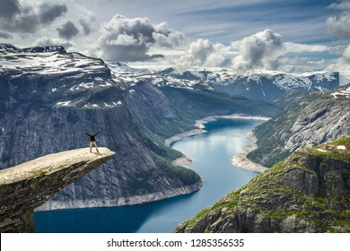 Man standing on top of a protruding rock over a fjord