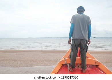 Man standing on wooden boat facing the ocean. Concept of fisherman.