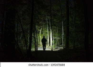 Man standing outdoor at dark night shining with flashlight. Mystical and abstract photo of Swedish nature and landscape.