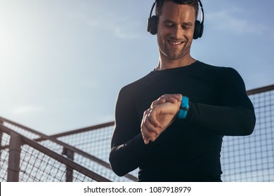 Man standing outdoors with headphones using a smartwatch to monitor his progress. Male athlete resting and checking his performance on fitness smartwatch device.