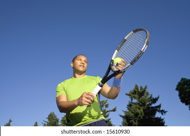 A man is standing outside on a tennis court.  He is holding a tennis racket, about to serve the ball, and looking away from the camera.  Horizontally framed shot.