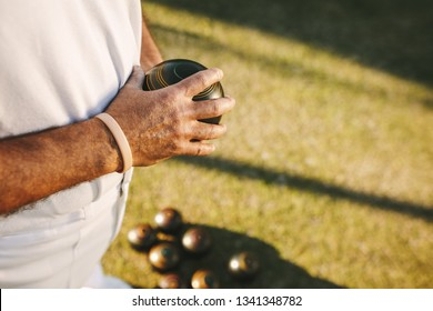 Man standing in a park playing boules on a sunny day. Person playing boules in a lawn standing with a boules in hand.
