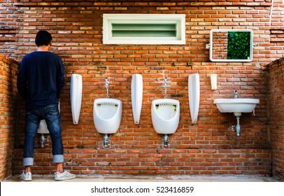 Man standing pee Brick wall public toilet exterior / outdoor