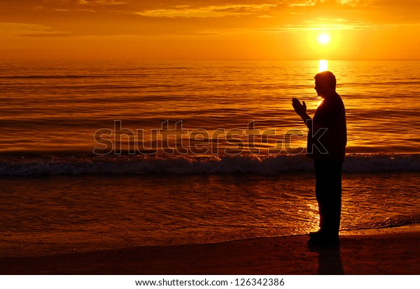Man standing and praying at the ocean with orange sunset in background