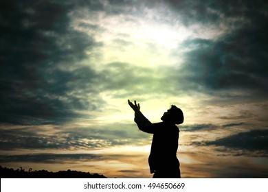 Man standing prays for god in nature morning light