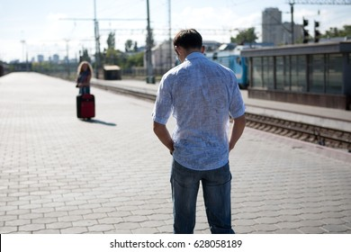 Man is standing at railway station and seeing off his girlfriend or wife