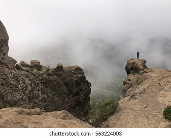 Man standing a rock at the Roque Nublo a volcanic rock on the island of Gran Canaria