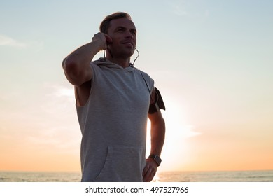 man standing in sunset after his workout