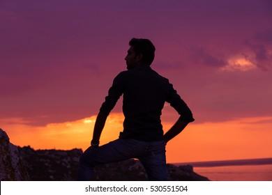 man standing thinking back light sunset lighting side view profile silhouette summer evening beach