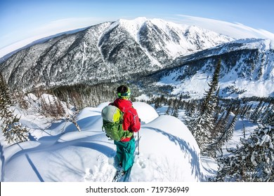 Man standing at top of ridge. Ski touring in mountains. Adventure winter freeride extreme sport.