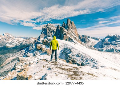Man standing at top of snowy mountain. Hiker wearing a yellow jacket and looking at a beautiful view. Outdoors and sport concepts in Italian Alps mountains.