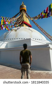 A man standing under Bouddhanath Temple in Kathmandu, Nepal. The temple has many colourful prayer flags with 'om mani padme hum' mantra written on them attached to it's golden rooftop. Spirituality
