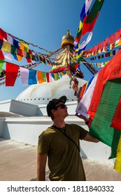 A man standing under the colourful prayer flags with 'om mani padme hum' mantra written on them attached to the golden rooftop of The Bouddhanath Temple in Kathmandu, Nepal. He is touching the flags