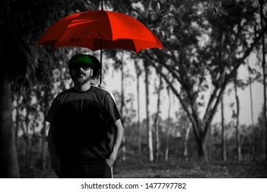 Man standing under a red umbrella unique photo