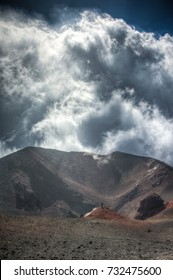 Man standing in a volcano crater on Mount Etna in Sicily, Italy on a cloudy autumn day.