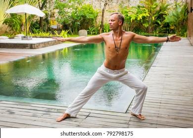 Man standing in warrior yoga pose