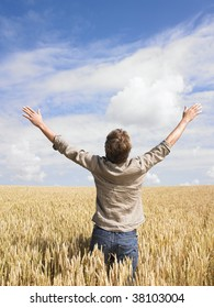 Man standing in wheat field opening arms