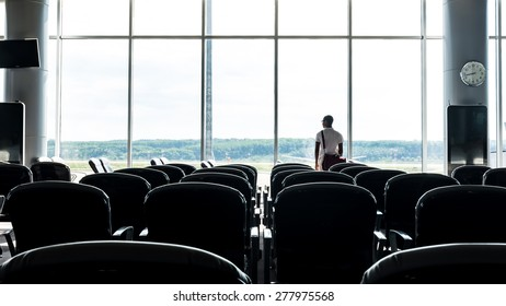 Man standing at the window lounge terminal of the airport Waiting for flight