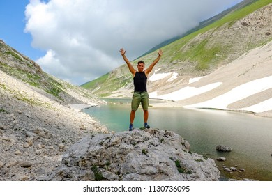 Man standing,with open arms,  over  big stone in Pilato lake, Sibillini mountains, Marche Italy. Meditation and relaxation concept
