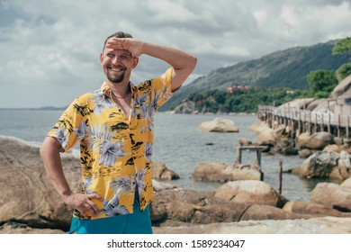 A man stands against a tropical landscape. Young guy wearing a hawaiian shirt on a tropical island. Handsome man and bright positive emotions.