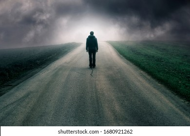 Man stands alone on dark cloudy road.