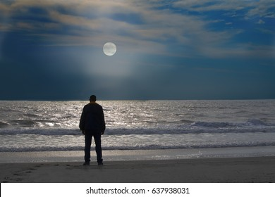 A man stands alone on at the edge of the  calm ocean  looking east in the evening as the moon rises