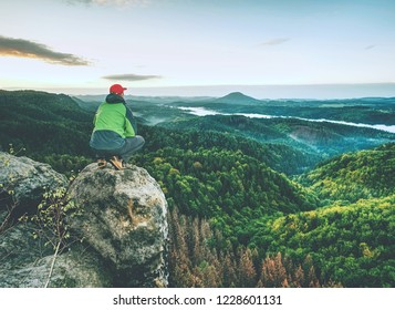 Man stands alone on the peak of rock. Hiker watching to autumn Sun at horizon . Beautiful moment