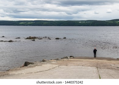 A man stands alone on a ramp looking out at the saguenay river on a dark evening in Quebec