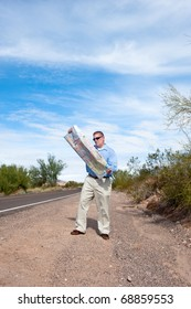 A man stands along a deserted road reading a roadmap