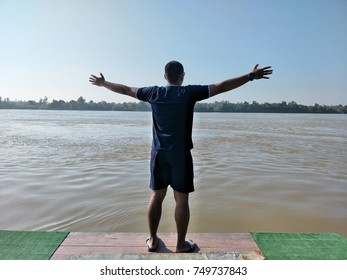 The man stands arms near the river.