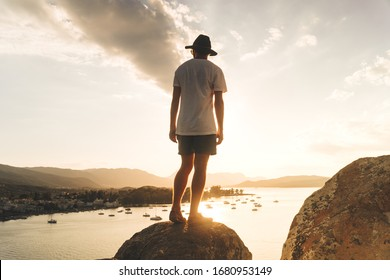 A man stands atop a boulder on a hill overlooking a sea filled with sailboats at sunset on the Greek island of Poros in summer.