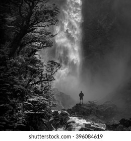 Man stands in awe in front of Devil's Punchbowl, a waterfall in Arthur's Pass N.P., New Zealand.