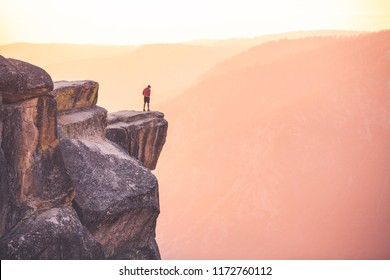 A man stands at the edge of a cliff at Taft Point,Yosemite National Park, California.