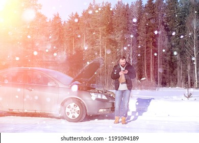 a man stands in front of a broken car in the winter