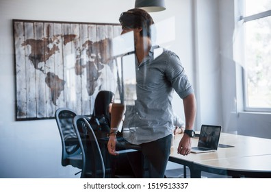Man stands in front of glass. Young business people in formal clothes working in the office.